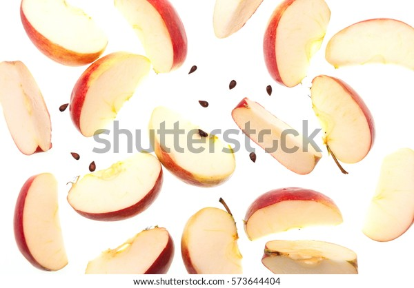 Slices of fresh red apple and seeds, isolated on white background, top view.