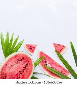 Slices of fresh watermelon on color background, with palm leaves. Top view. Copy space
