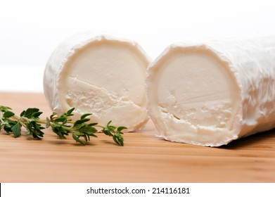 Slices of Goat cheese seasoned with Thyme. Displayed on a cutting board of Bamboo.