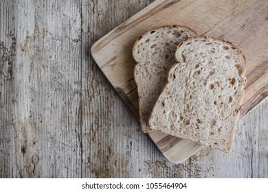Slices of granary bread on breadboard