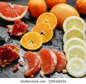 Slices of grapefruit, lemon and pomegranate in the black background.