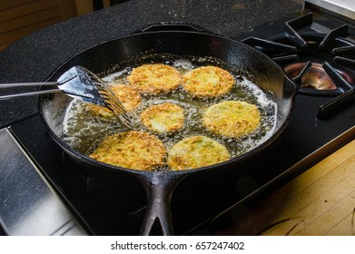 Slices of green tomato being fried to make fried green tomatoes