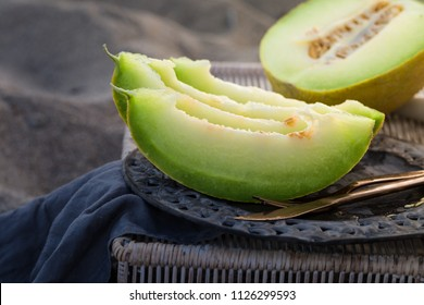 Slices of green yellow melon canteloupe on dark vintage plate on bamboo straw basket table, knife and fork, picnic concept by the beach on sand, summer outdoors snack fruits, copy space