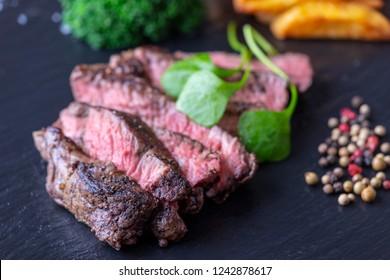 slices of a grilled steak on slate