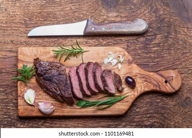 slices of a grilled steak on wood