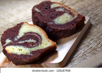 Slices of homemade marble cake on a wooden plate with brown backround