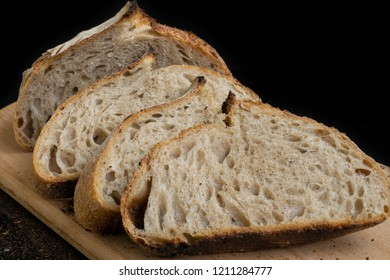 Slices of homemade sourdough bread on wooden board crumb texture close up homemade healthy food.
