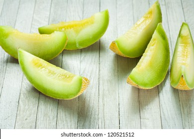 slices of honeydew melon on white wooden table