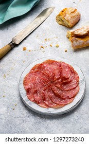 Slices of italian salami on small round cutting board on delicate background