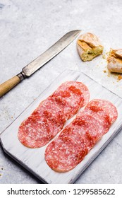 Slices of italian salami on small cutting board on delicate background
