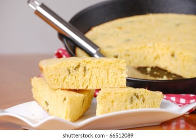 Slices of Jalapeno Cornbread on a White Plate with Cast Iron Pan in the background