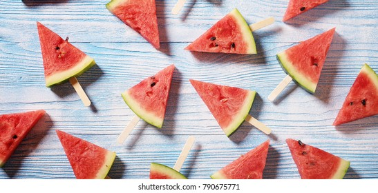 Slices of juicy red watermelon on a wooden blue background