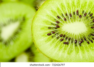 Slices of kiwi fruit on kiwi background.