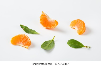 slices and leaves of ripe tangerine on white background