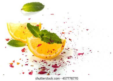 slices of lemon and a sprig of mint on a white background. scattered petals of a tea rose