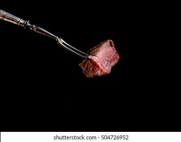 Slices of Medium rare grilled Steak Ribeye on meat fork on  black background