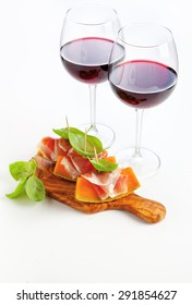 Slices of melon cantaloupe with prosciutto ham & wineglasses with wine. healthy snack