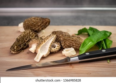 Slices of morel mushrooms, wild garlic and knife on wooden board - detail from kitchen