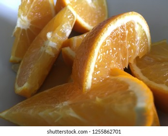 Slices of Orange in the bowl over wooden table