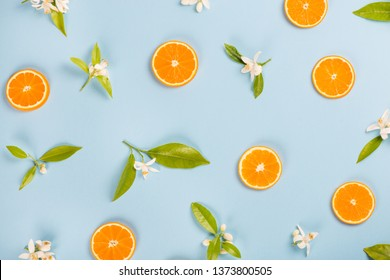 Slices of orange fruit and blossom with leaves on a blue background, above view.