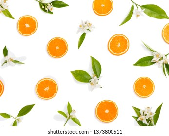 Slices of orange fruit and blossom with leaves, above view.
