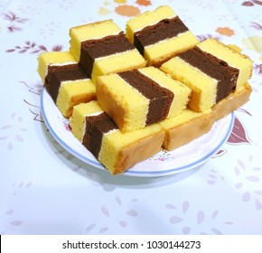 Slices of orange Lapis Surabaya cake have fabulous texture and give taste of orange and chocolate with berries jam melted together in between layers.