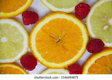 slices of orange and lemon and raspberries on white. Looks like a background