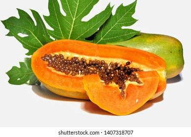 Slices of papaya with green leaves isolated on white background. Tropical fruit concept