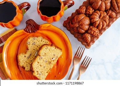 Slices of pecan pumpkin bread sitting on pumpkin shaped plate with two cups of coffee and a whole loaf of bread made in decorative pan with space for text