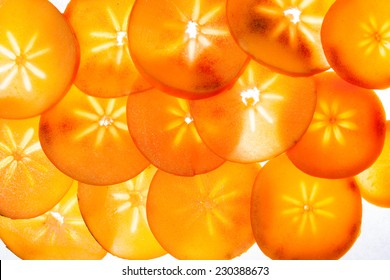 Slices of persimon fruit, illuminated from behind
