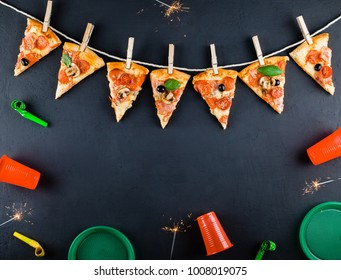 Slices of pizza in the form of a garland with the attributes of a party and Bengal Candles. Pizza slices on a gray background. Space for text. Pizza menu. Birthday with fast food. Conceptual