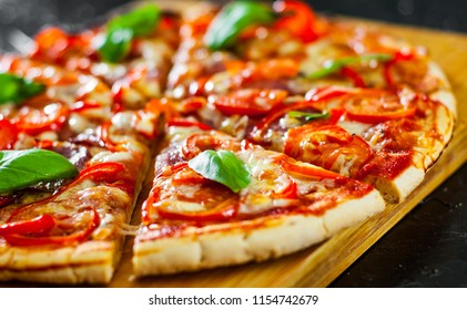 slices of Pizza with Mozzarella cheese, Ham, Tomatoes, salami, pepper, pepperoni Spices and Fresh Basil. Italian pizza