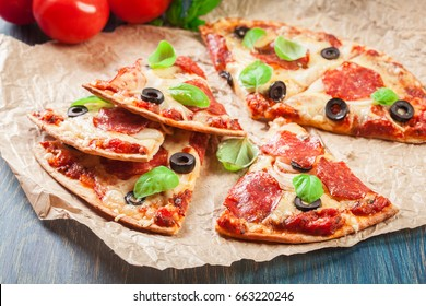 Slices of pizza pepperoni with olives served on a paper