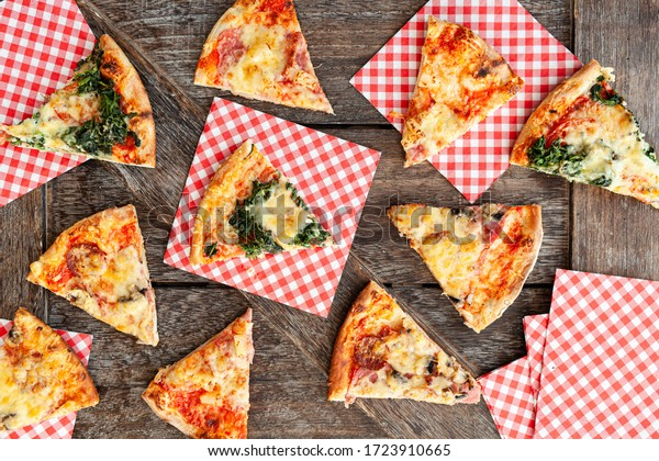 Slices of pizza with plaid napkins on a wooden background