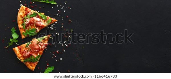Slices of pizza with prosciutto and spices on black background, copy space, top view