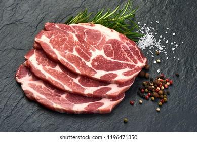 slices pork loin with herbs on a slate shale plate