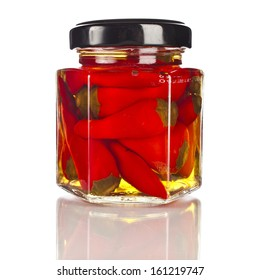 Slices of preserved red hot  pepper in glass jar close up isolated on a white background