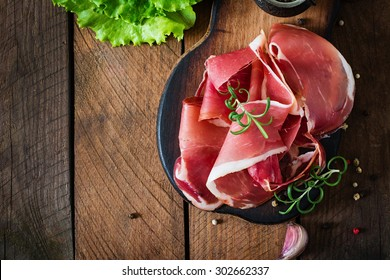 Slices of Prosciutto on old wooden background. Top view