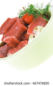 slices of raw fresh beef meat fillet in a ceramic dish with garlic and red peppers isolated over white background . shallow dof