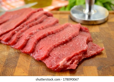 slices of raw meat on cutting boarb