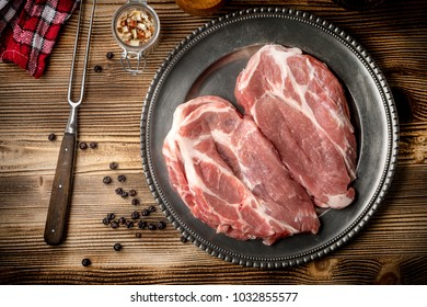 Slices of raw pork neck on a metal plate. Top view.