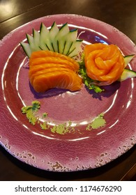 Slices of raw salmon or salmon sashimi with slices of cucumber, lettuce, radish, ginger and wasabi