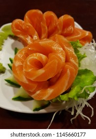Slices of raw salmon or salmon sashimi garnished with slices of cucumber, lettuce, radish and wasabi