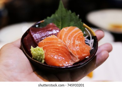 Slices of raw Salmon Sashimi recipe on hand in Japanese restaurant. This menu is one of popular Japanese food in  the worldwide.