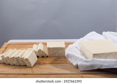 Slices of raw tofu on cutting board