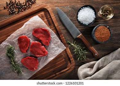 Slices of raw veal calf meat on white cooking paper and wooden cutting board.. Decorated with herbs, spices and chef's knife. Overhead view.