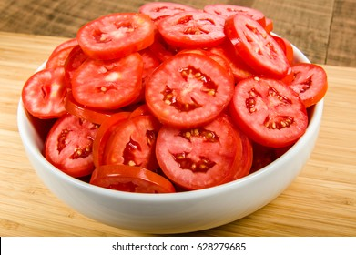 Slices of red tomatoes in a white bowl