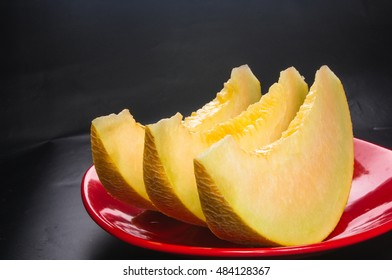 slices of ripe juicy melon in red plate on black background