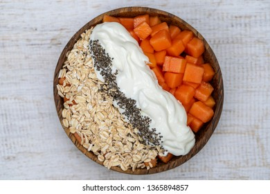 Slices of ripe sweet papaya fruit with oat flakes, chia seeds and white yogurt on coconut bowl on white wooden background, close up . The concept of healthy eating