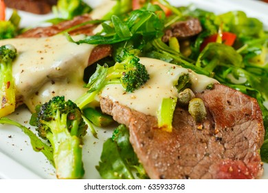 Slices of roast beef with cream sauce, broccoli and arugula salad